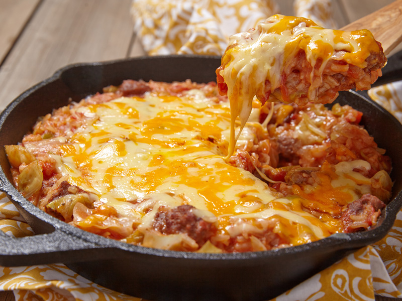 Cheesy Beef Mixture in Cast Iron Skillet being scooped with a wooden spoon