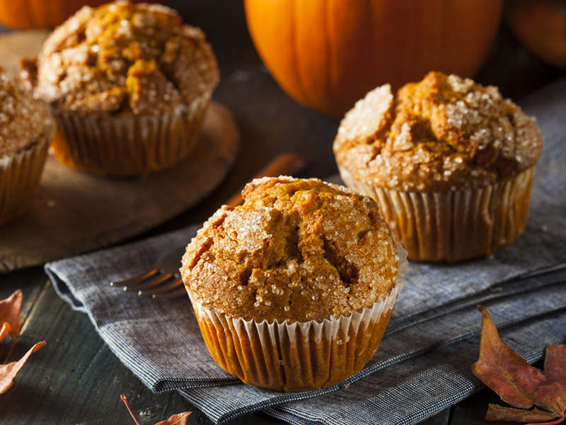 pumpkin muffins in front of a pumpkin on a table