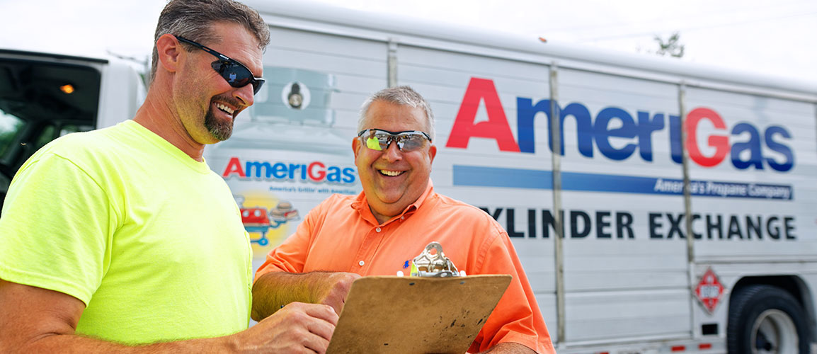 Two men with clipboard in front of an AmeriGas truck.