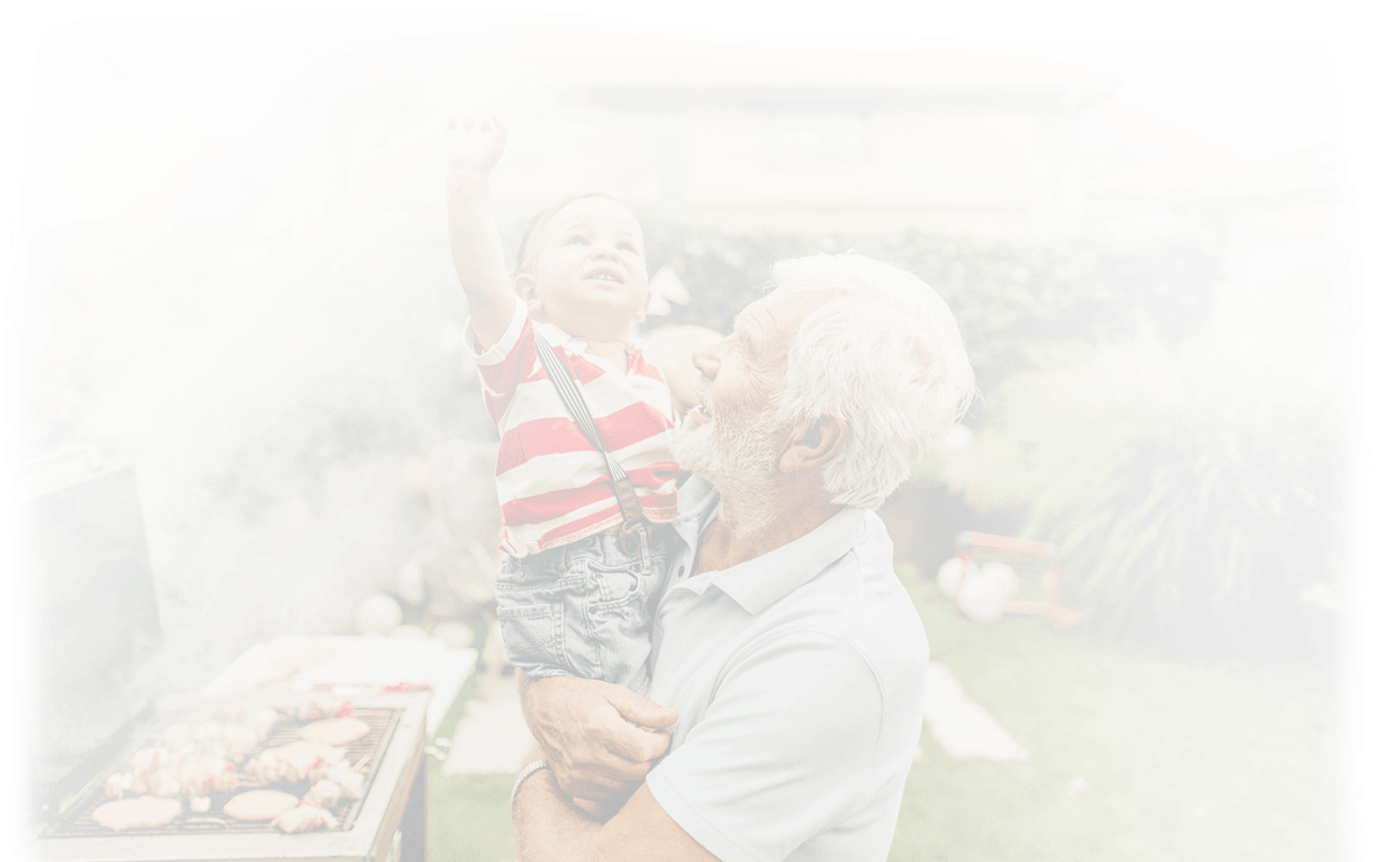 man holding child in a backyard next to a grill
