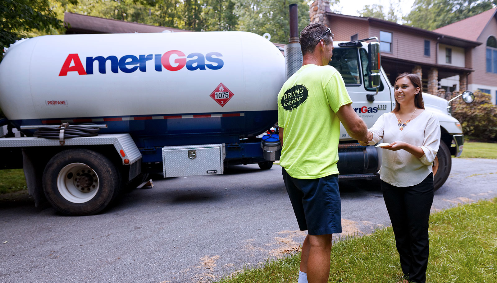 Man and woman shake hands in front of Amerigas truck