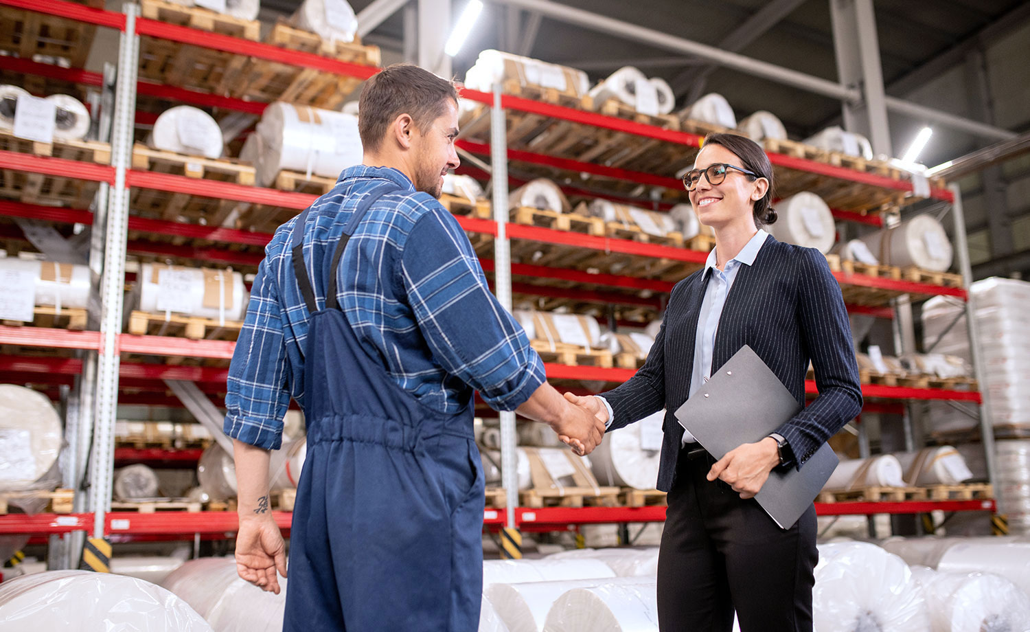 Business partners shaking hands in a warehouse.
