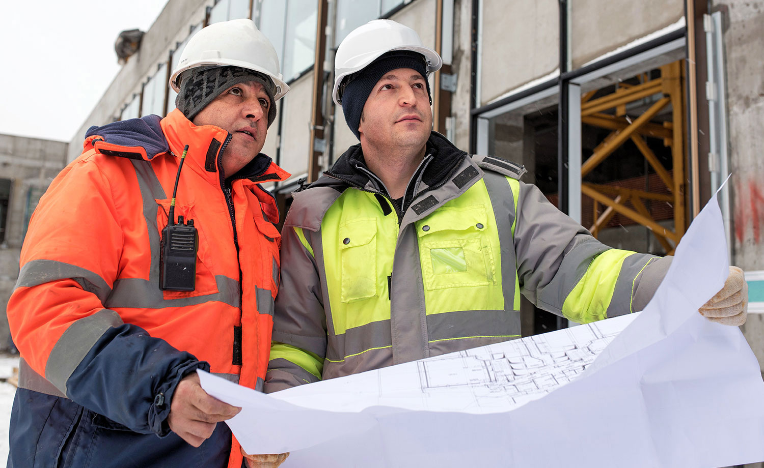Two men in hard hats looking over plans.
