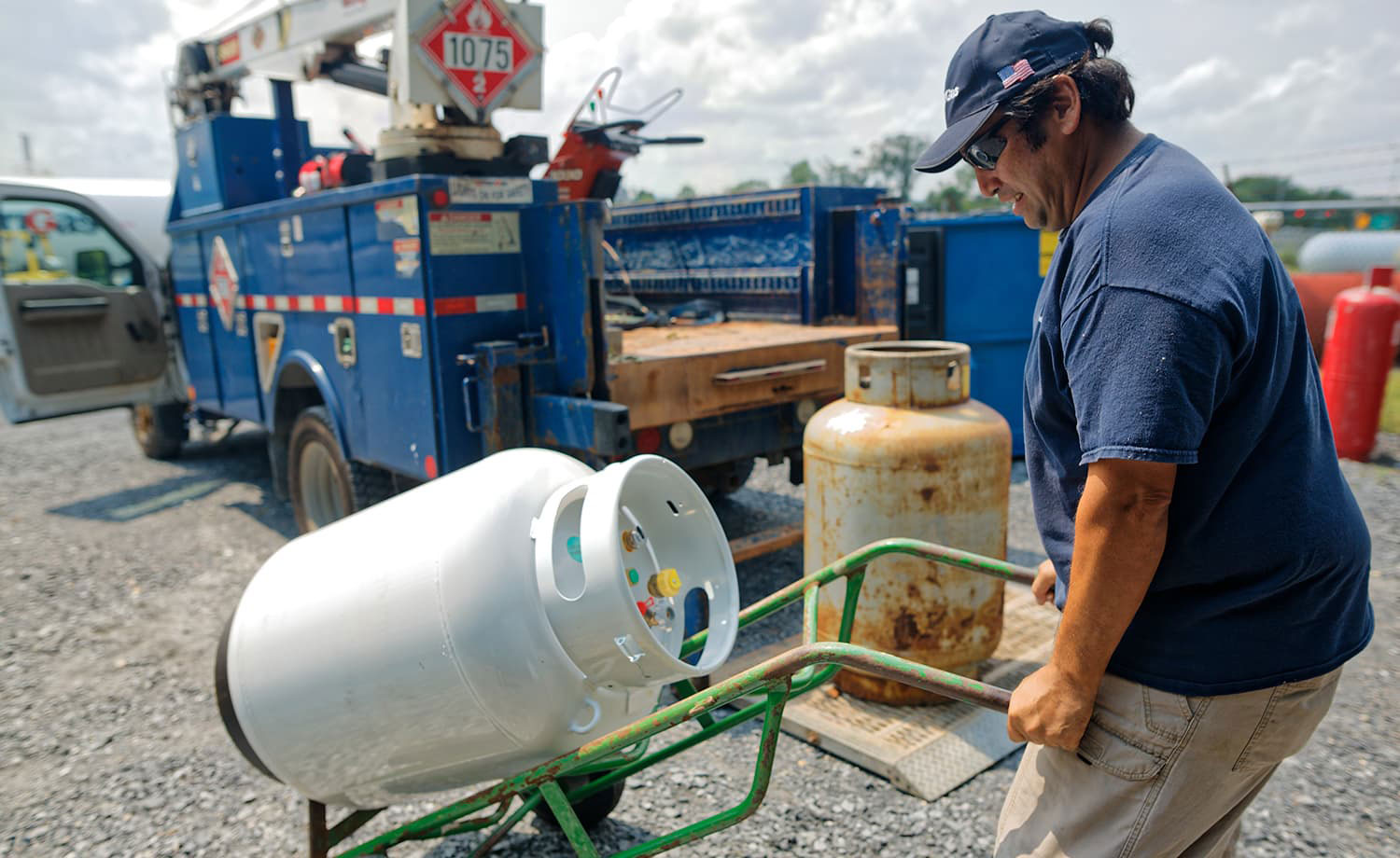 Man moving propane tank with a hand truck.
