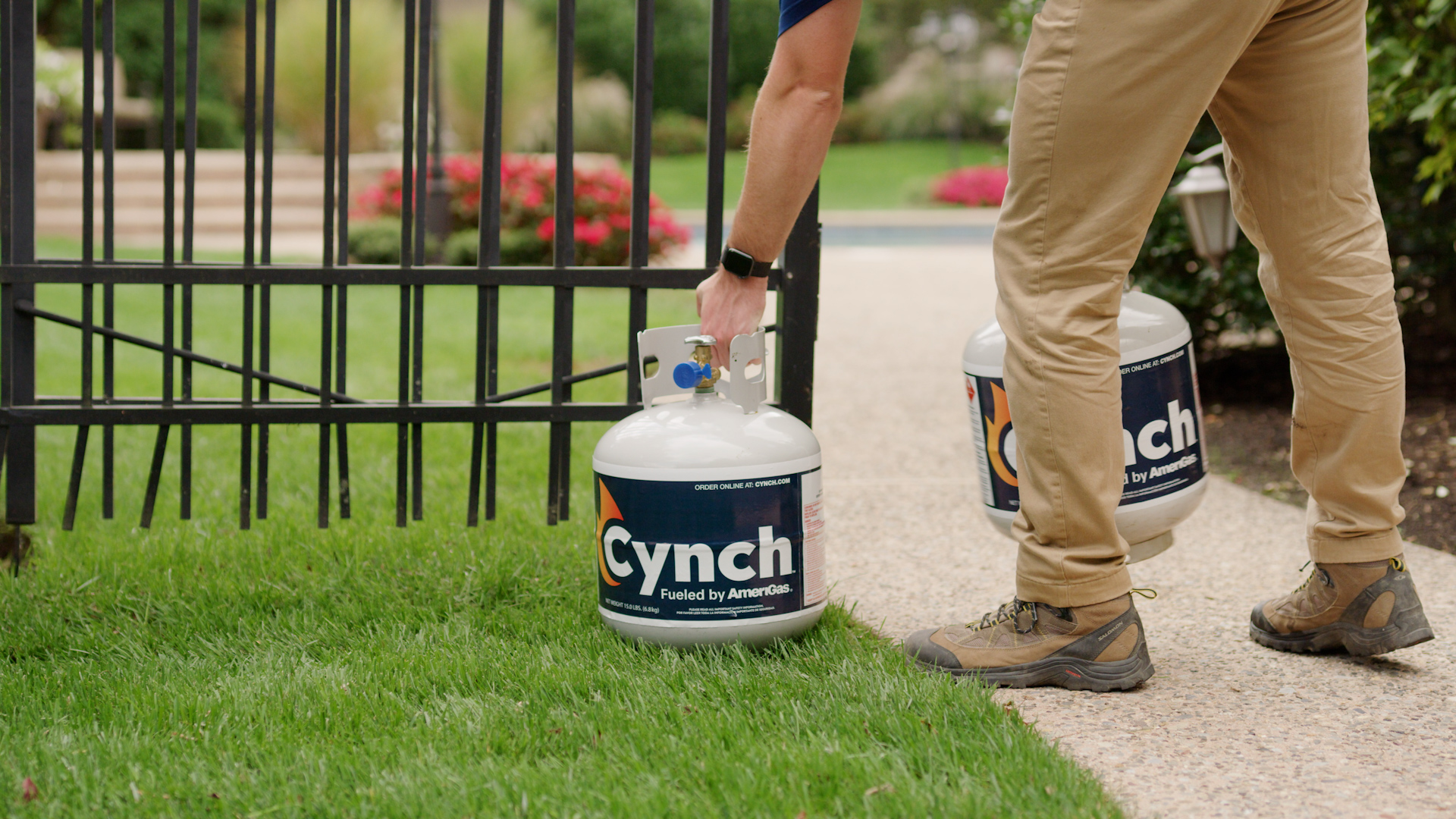 Person picking up Cynch branded portable propane tank