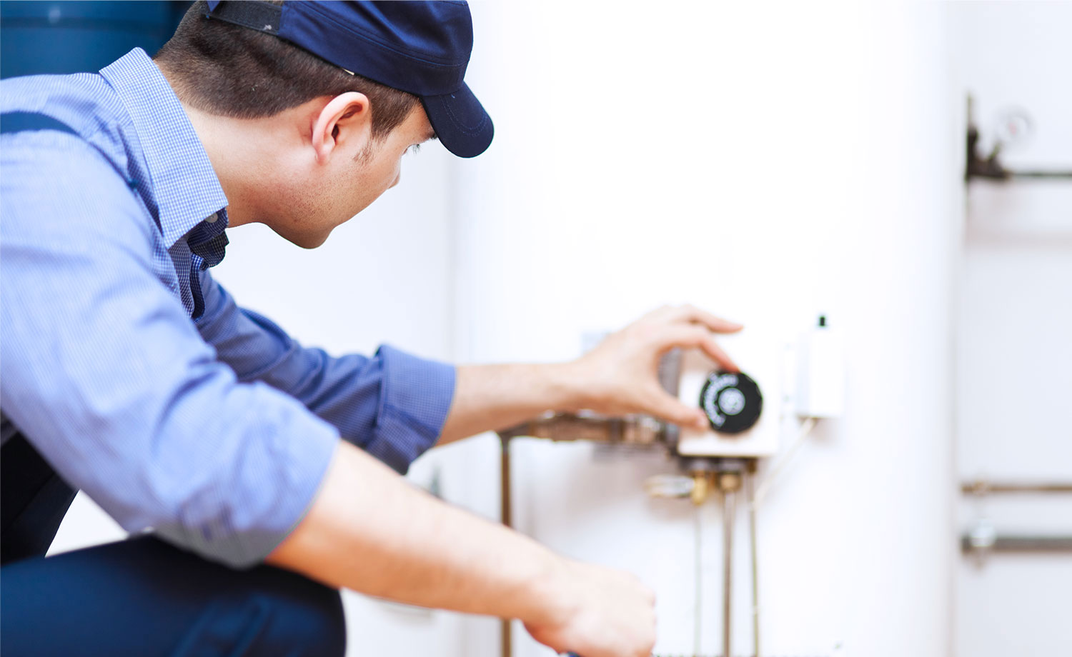 Inspector looking at water heater thermostat.