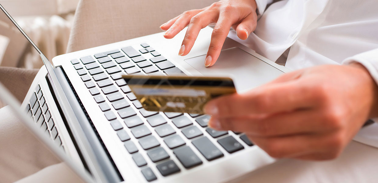 Person holding credit card in front of a laptop.